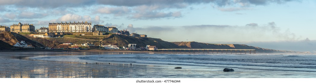 Panorama of the beach of Saltburn-by-the-Sea, Redcar and Cleveland, England, UK at low tide showing the pier, cliffs and sea front at sunrise.