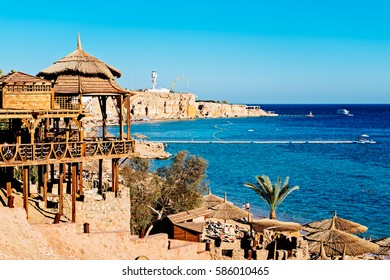 Panorama of the beach with umbrellas at the reef on sunset, Sharm el Sheikh, Egypt