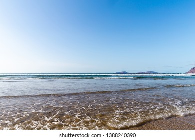 Panorama of beautiful beach and tropical sea of Lanzarote. Canaries. Coast of Famara beach, Lanzarote Island, Canary Islands. Tourists on the most popular beach at the island of Lanzarote.