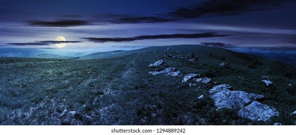 panorama of beautiful carpathian alpine meadows at night in full moon light. wonderful summer landscape. stones on the edge of a hill