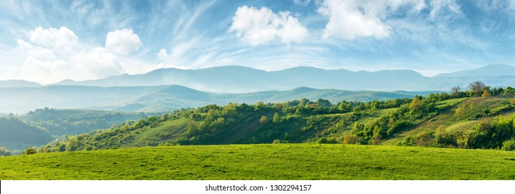 Photo of panorama of beautiful countryside of romania. sunny afternoon. wonderful springtime landscape in mountains. grassy field and rolling hills. rural scenery