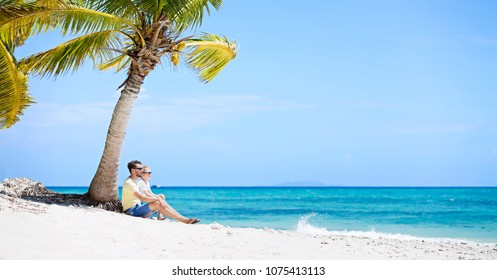 panorama of beautiful family of two, father and son, sitting together at the beach by palm tree in the background enjoying summer vacation, white sand beach and turquoise lagoon, copy space on right