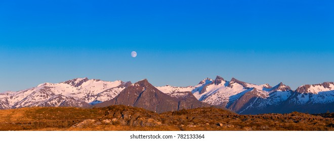 Panorama Of Beautiful Midnight Sun Scene, Mountain With Snow, Moon Over Mountain, Lofoten Islands, Norway