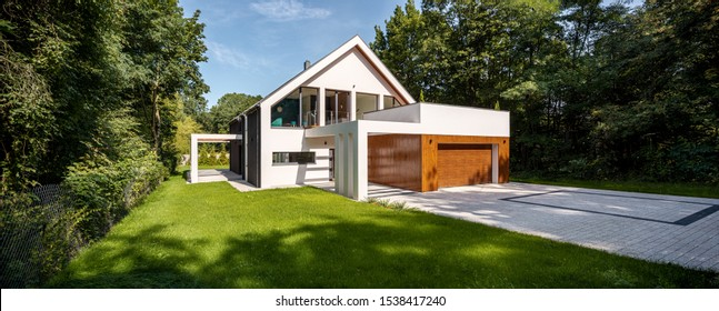 Panorama of beautiful and modern house among trees, exterior view