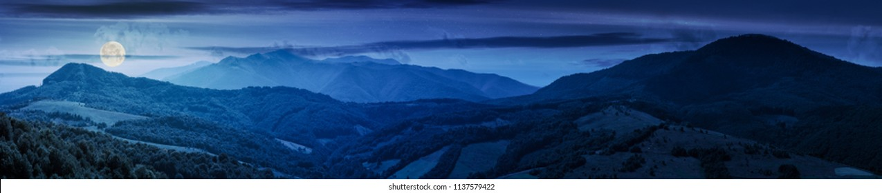 panorama of beautiful mountain ridge at night in full moon light. perfect countryside landscape. rural field on the nearest forested hills. Mighty Borzhava ridge in the distance