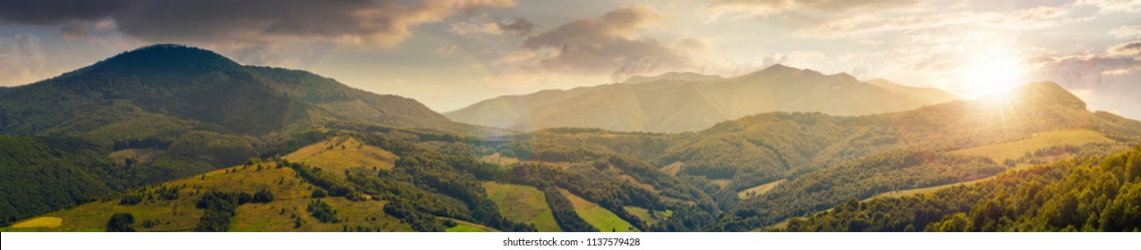 panorama of beautiful mountain ridge at sunset in evening light. perfect countryside landscape. rural field on the nearest forested hills. Mighty Borzhava ridge in the distance
