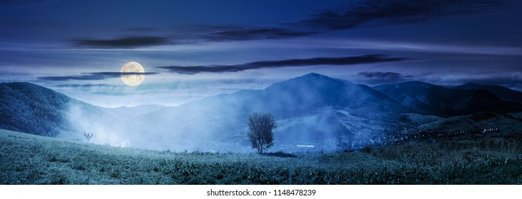 panorama of beautiful mountainous countryside at night in full moon light. tree on the hill side in smoke from fire in the valley. wonderful bright autumn landscape with gorgeous cloudscape