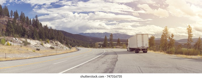 A panorama of beautiful mountainous landscape with a highway running through it and a truck driver has stopped the 18-wheeler on the shoulder