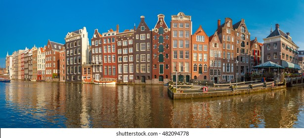 Panorama of beautiful typical Dutch dancing houses at the Amsterdam canal Damrak in sunny day, Holland, Netherlands.