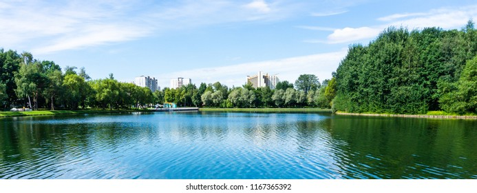 Panorama of big park and lake in megapolis at summer