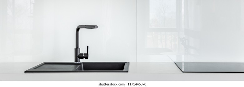 Panorama of black kitchen sink on high gloss white countertop