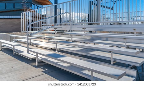 Panorama Bleachers with railings against a building and cloudy blue sky
