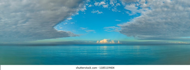 Panorama of blue sky with puffy clouds over the sea. Ocean with aqua colours. High resolution panoramic sky.