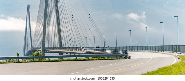 Panorama of bridge and car road in Norway, Europe. Auto travel through scandinavia. Mountain and clouds in background.
