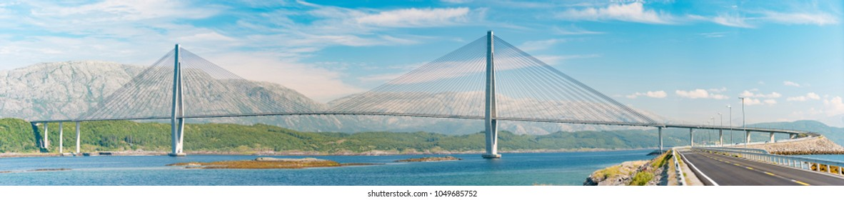 Panorama of bridge and car road in Norway, Europe. Auto travel through scandinavia. Blue cloudy sky, lake and bridge in background.
