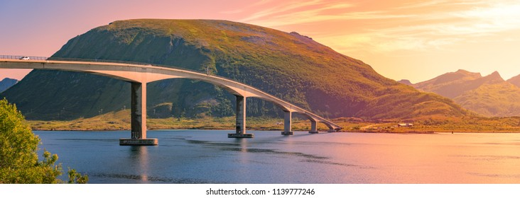 Panorama of bridge and car road in Norway, Europe. Auto travel through scandinavia. Sunset with mountain and clouds in background.