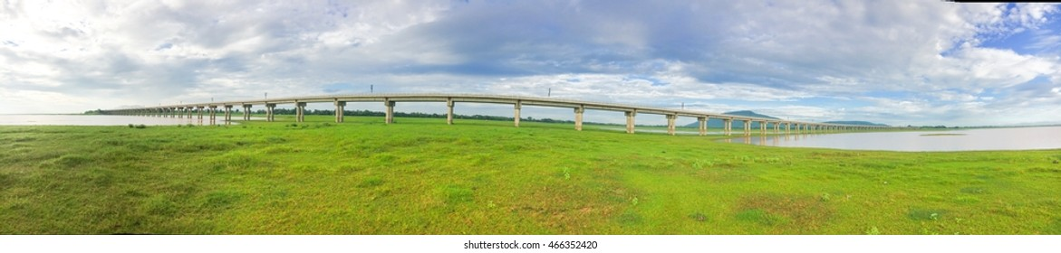 Panorama of bridge railway transportation cross over grass field in the dam of Thailand.