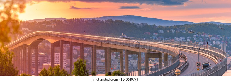 Panorama of bridge in Tromso and car road in Norway, Europe. Auto travel through scandinavia. Sunset with mountain and clouds in background.