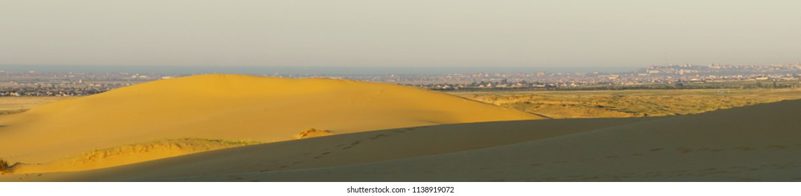 Panorama of the bright desert mountain barkhan Sarykum with yellow-golden sand and the Caucasus Mountains at sunset, Dagestan, Caucasus
