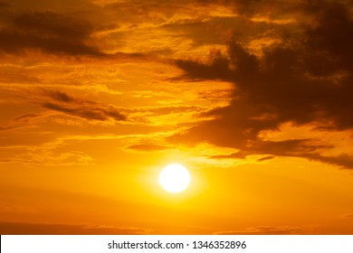 Panorama of brightly yellow sun on the orange sky with clouds at golden hour natue background sunrise or sunset scene