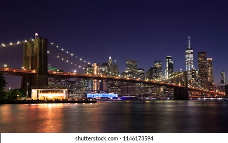 Panorama of Brooklyn Bridge and New York City (Lower Manhattan) with lights and reflections, USA
