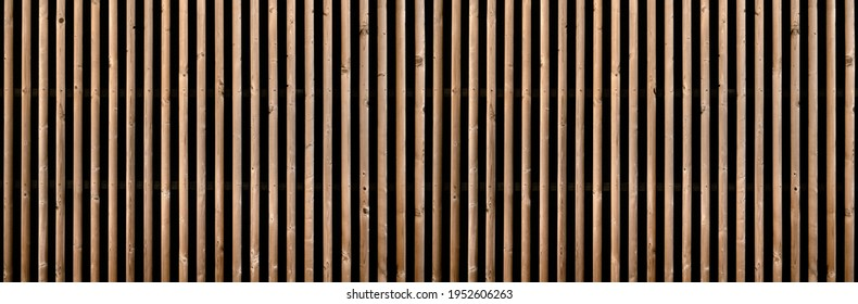 Panorama of a brown slatted partition wall with two rows of small brackets in front of dark background