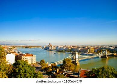 Panorama of Budapest, Hungary. Landscape with Hungarian Parliament Building, Margit island and Chain bridge over Danube river. Autumn cityscape with blue water. Sunny day and cloudless sky in Europe.