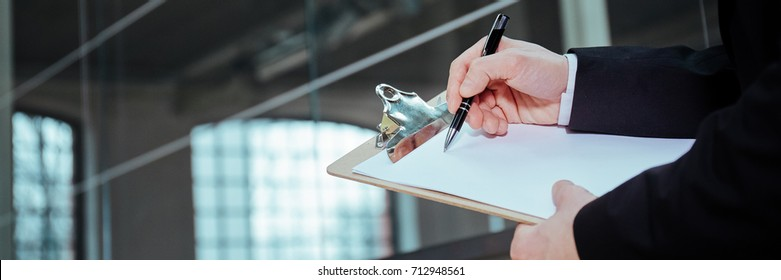 Panorama of businessman with clipboard and pen, close up