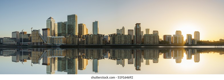 Panorama of Canary Wharf business district with water reflection at sunset