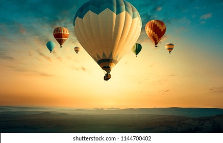 Panorama of Cappadocia skyline at sunrise - multicolored hot air balloons above mountains landscape. Goreme valley at sunset for your travel concept or horizontal billboard on Turkey in retro style.