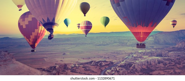 Panorama of Cappadocia at sunrise - multicolored hot air balloons above mountain. Wide landscape of Goreme valley in Turkey - your travel concept in retro style with effect of instagram filters.