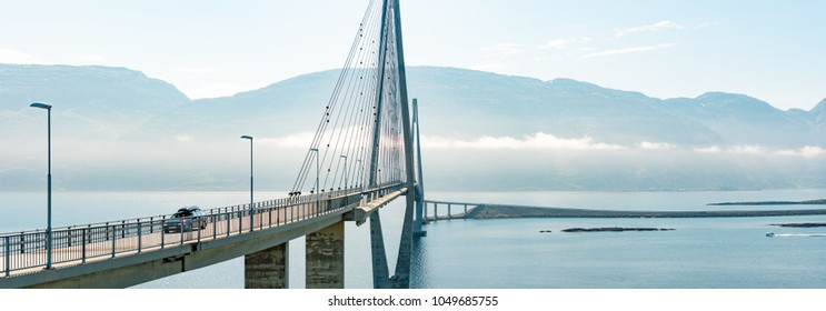 Panorama of car on road in Norway, Europe. Auto travel through scandinavia. Blue cloudy sky, lake and bridge in background.