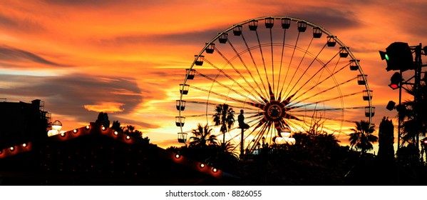 Panorama of a carnival silhouetted against the evening skyline at dusk.