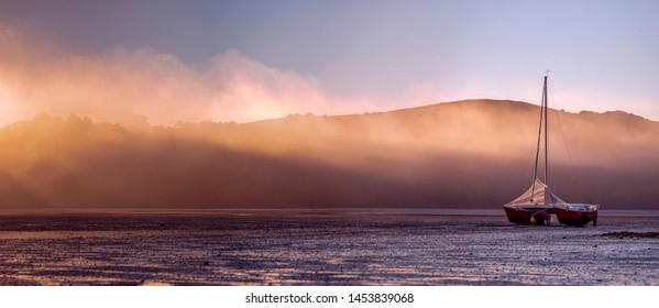 Panorama of a Catamaran Yacht Beached in a Harbor with Morning Fog  Mist and Sun Rays