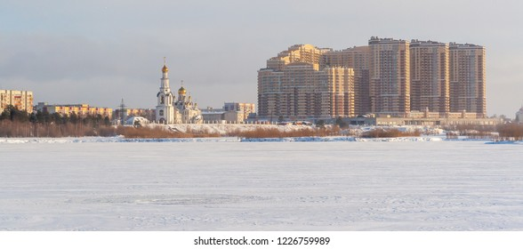 "Panorama The Cathedral of the Transfiguration in Surgut on a winter day near the modern residential complex ""Renaissance"". View from the river Ob."
