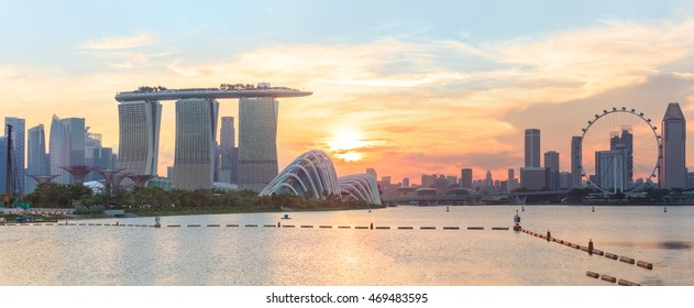 Panorama of central Singapore with water on foreground. Modern city architecture at sunset