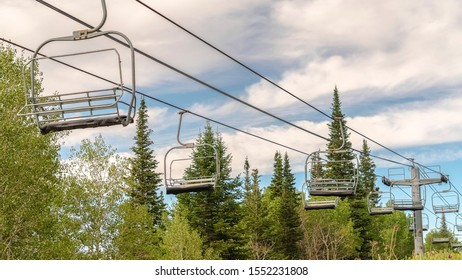 Panorama Chairlifts on cables with view of ski resort covered in greenery during summer