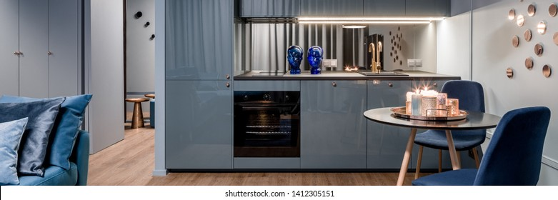 Panorama of charming kitchen interior in blue with stylish dining area and golden decoration