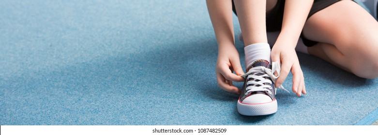 Panorama of child tying his shoes before sport activities