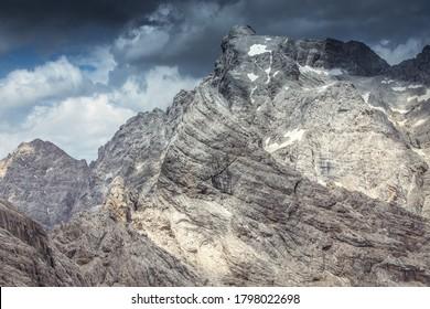 Panorama of Cima dei Preti summit with dramatic cloudy sky, Dolomites, Italy
