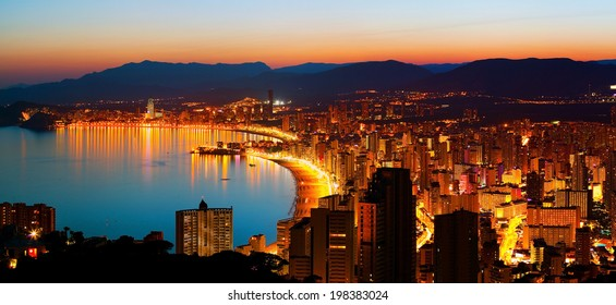Panorama of the city with an empty sea beach on a background of mountains in sunset (Spain, Benidorm)