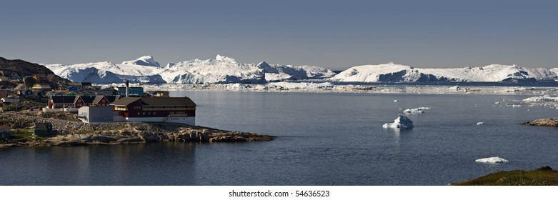 Panorama of the city of Illjulisat and a wall of icebergs. Greenland.