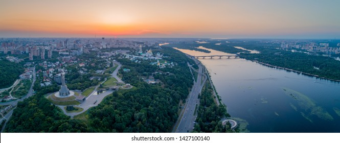 Panorama of the city of Kiev, the capital of Ukraine. Panorama of Kiev in a warm summer evening at sunset with shades of orange. Photo of Kiev from the drone, a bird's eye view.