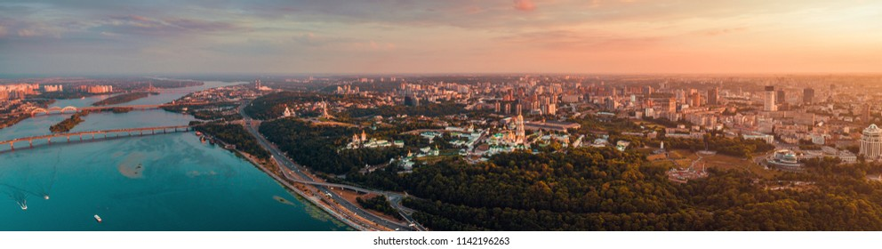 Panorama of the city of Kiev at sunset. A modern metropolis in the center of Europe against the backdrop of sunset sky from a bird's eye view. Aerial view. Panorama of the Tourist Center of Kiev. View