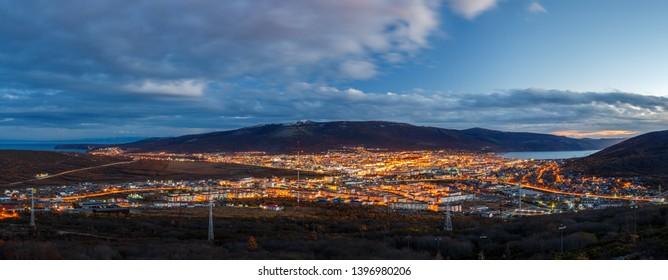 Panorama of the city of Magadan. Top view of a large northern city. Beautiful evening cityscape. Bright street lighting at dusk. Magadan, Magadan Region, Siberia, Far East of Russia. Panoramic photo.