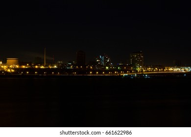 Panorama of the city at night. River in the foreground.