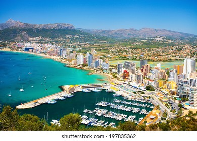 Panorama of the city on the seafront with people relaxing on the beach and yachts in the bay (Spain, Calpe)