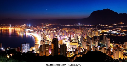 Panorama of the city and the sea coast at sunset on a background of mountains (Spain, Benidorm)