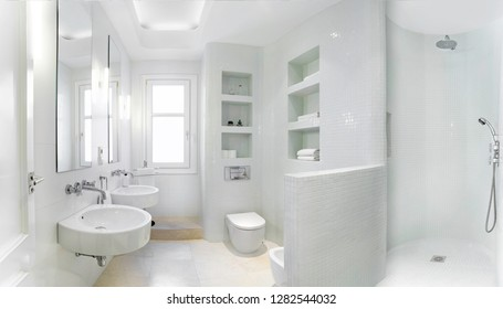 Panorama of a clean bright bathroom interior with vintage steel faucet and white tiles. Original designed space with modern pieces