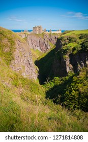 Panorama of a cliff with ancient castle in a bay with blue sky and white clouds in Dunnottar Castle, near Stonehaven, Aberdeenshire